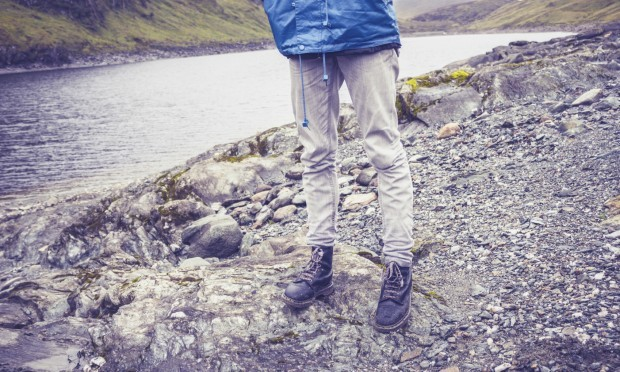 Close up on hillwalkers feet and legs by water to illustrate walks in Scotland