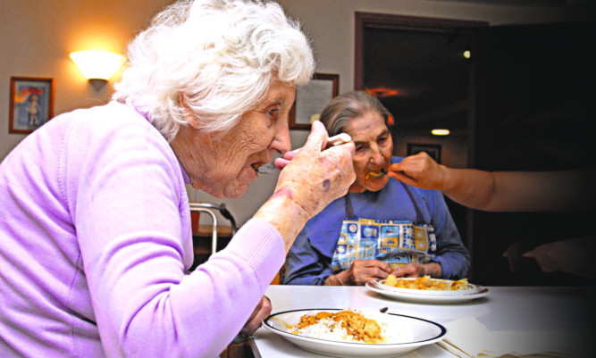 Elderly women in care home for people suffering from dementia at lunchtime London, UK,