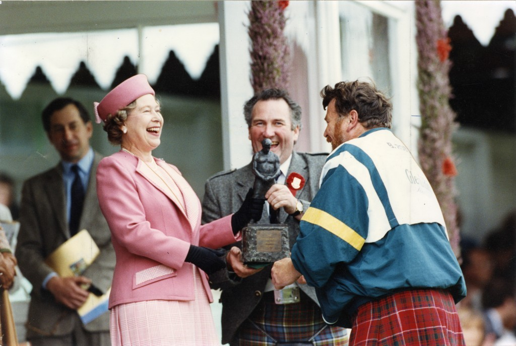 The Queen laughs as she presents Braemar caber champ Brian Robin with his trophy (DC Thomson)