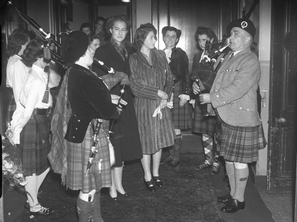 The Princess looks on as a pair of pipers belt out some tunes in 1945. It's hard to tell from the young royal's face if she's a fan of the skirl or not (DC Thomson)