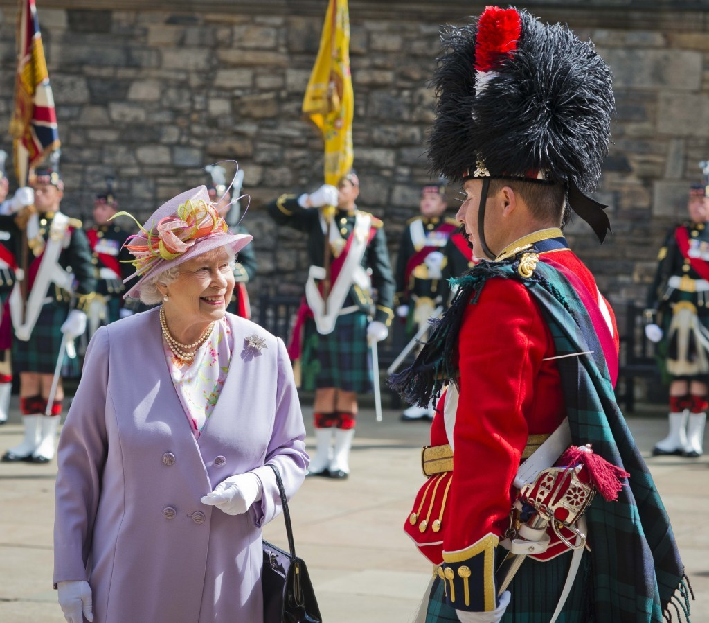 A smiling Queen Elizabeth is surrounded by soldiers in full Scottish dress at a commemorative service at the Scottish National War Memorial at Edinburgh Castle, 2014 (Chris Watt/Getty Images)