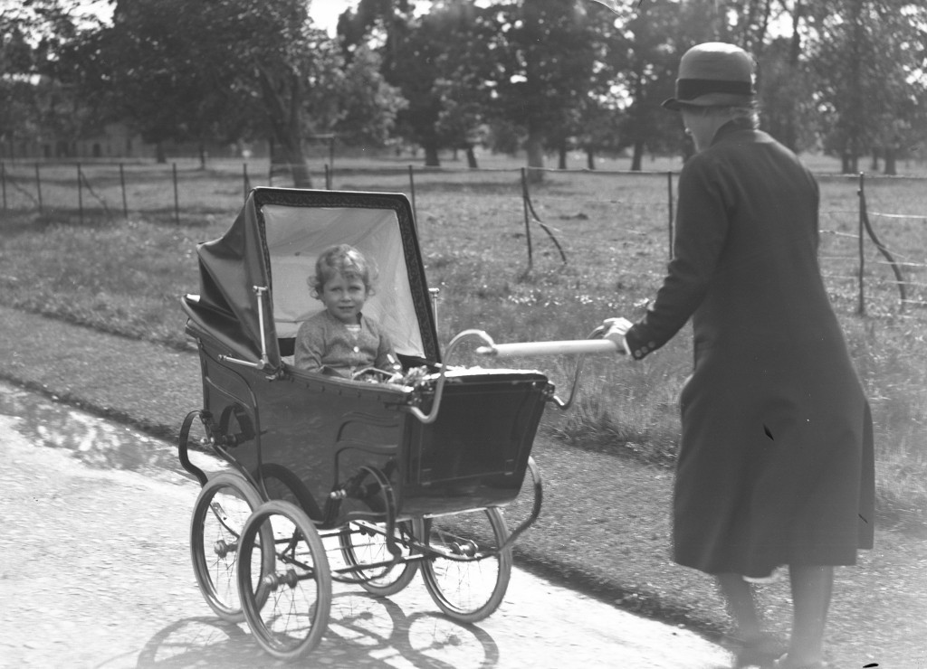 Princess Elizabeth sits up as she is pushed in a pram by an unknown woman in the grounds of Glamis (DC Thomson)