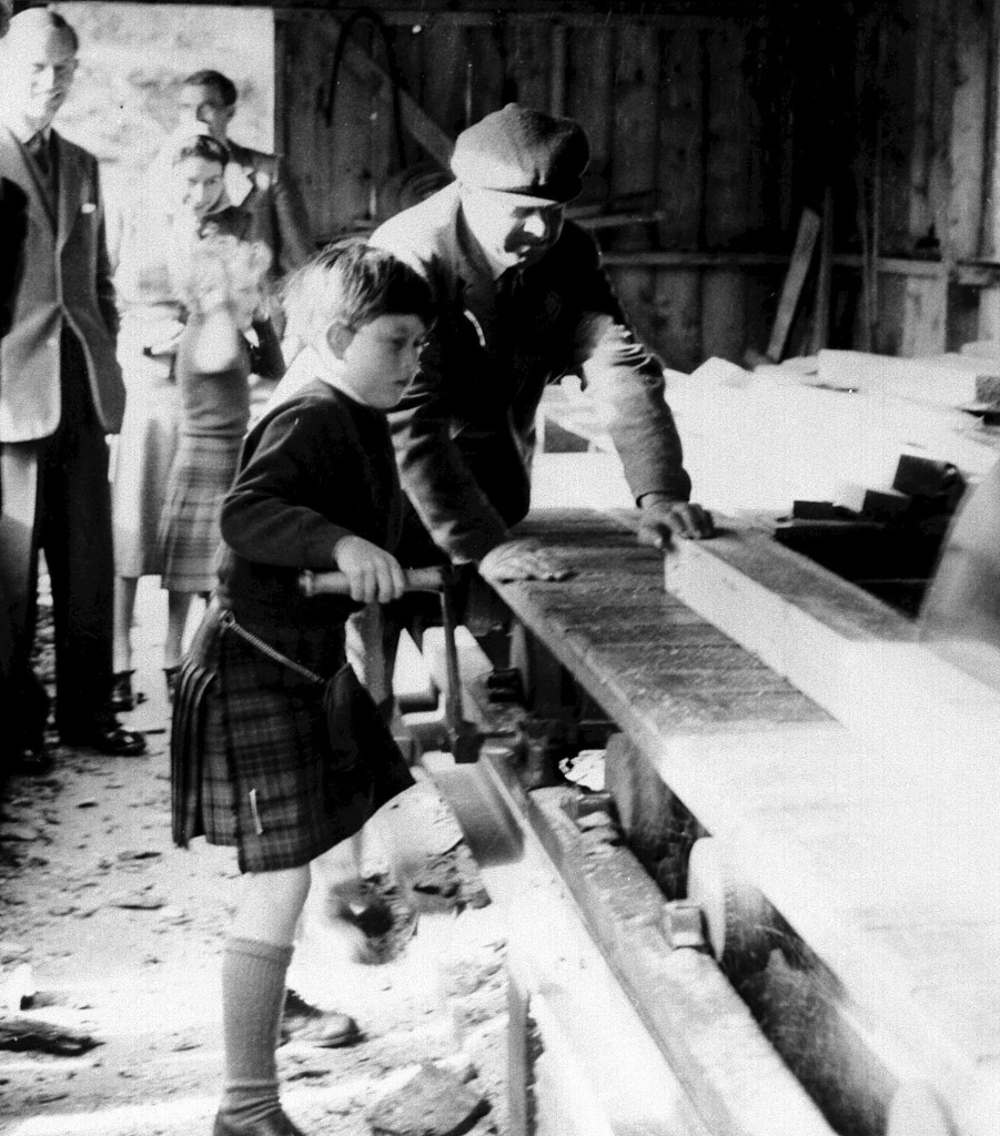 Eight-year-old Prince Charles tries his hand at the saw-mill on the Balmoral estate (PA Archive)