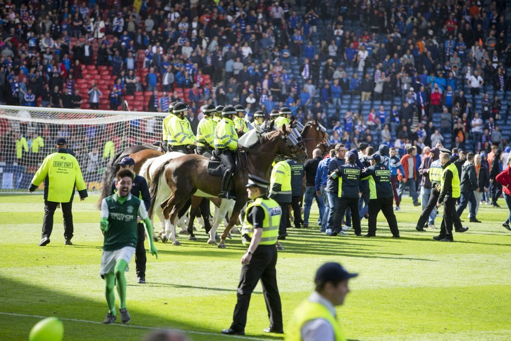 Police horses try to guide fans off the pitch (Jeff Holmes/PA Wire)