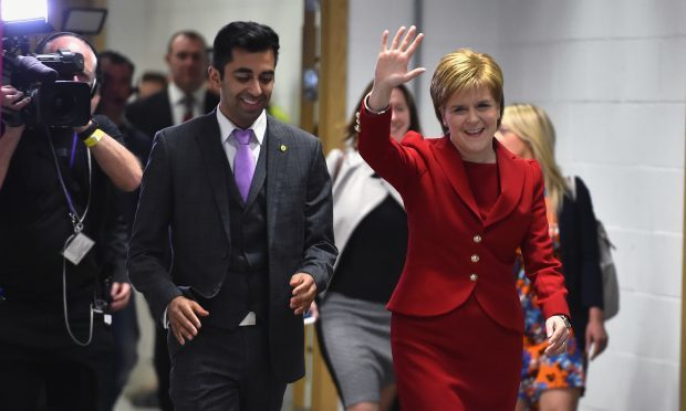 SNP leader Nicola Sturgeon arrives with Humza Yousaf at the count for the Scottish Parliament elections at the Emirates Arena (Jeff J Mitchell/Getty Images)