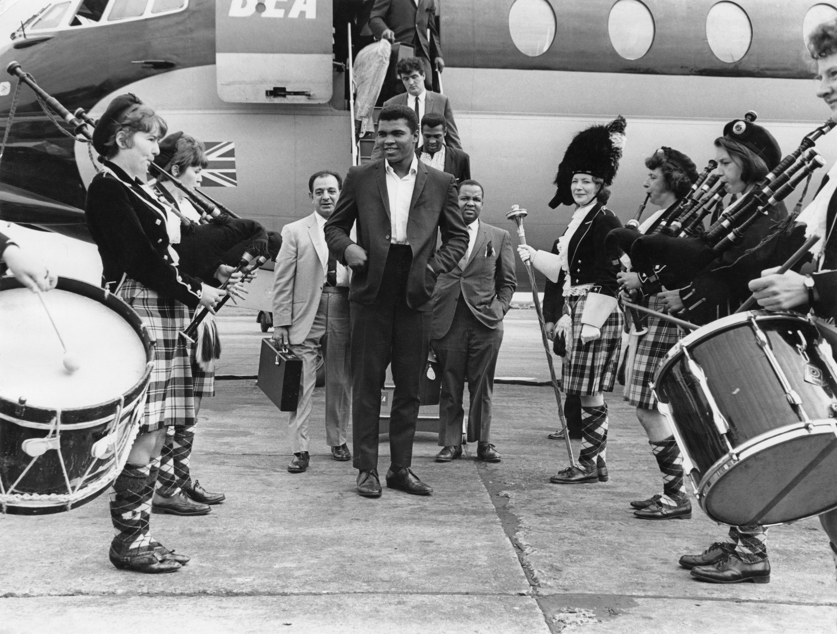 Muhammad Ali is greeted by a traditional Scottish pipe band on his arrival at Glasgow Airport, 18th August 1965 (Daily Express/Pictorial Parade/Archive Photos/Getty Images)
