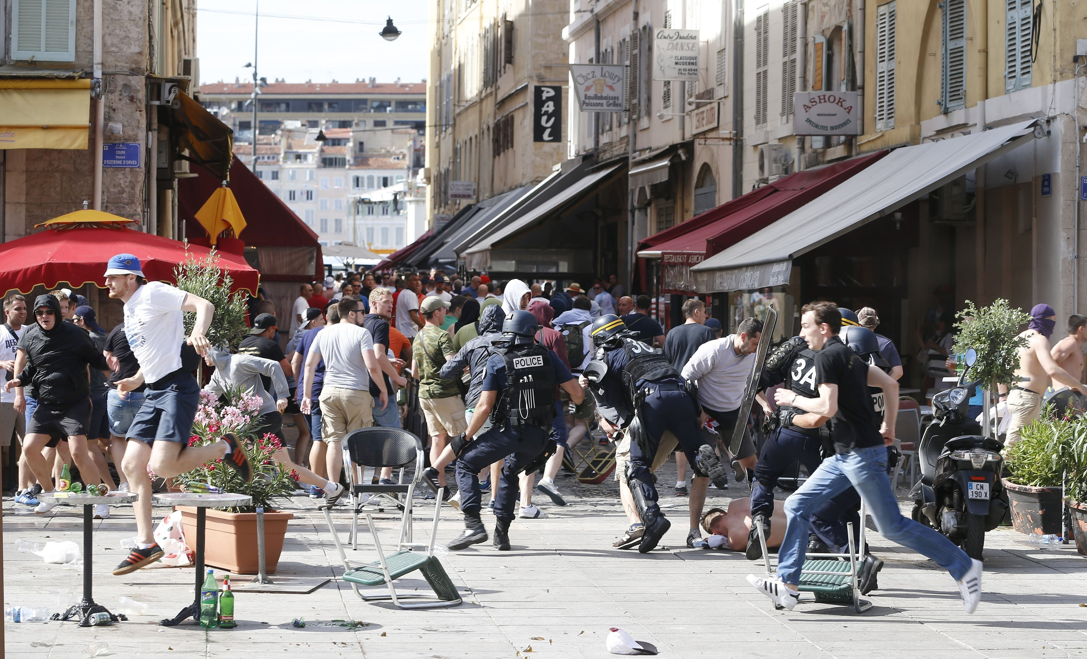 French police officers charge supporters during clashes in downtown Marseille, France (AP Photo/Darko Bandic)