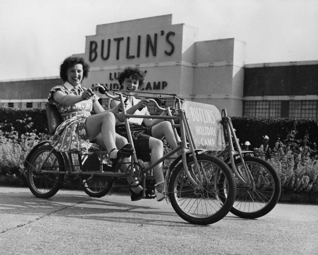 Two holidaymakers riding a bicycle for two at Butlin's Holiday Camp in Clacton (Hulton Archive/Getty Images)