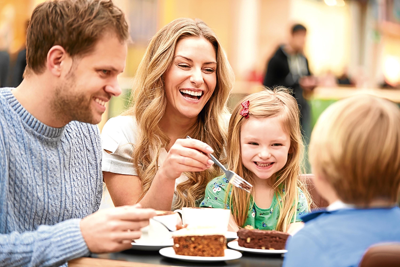 Family Enjoying Snack In Café Together Smiling