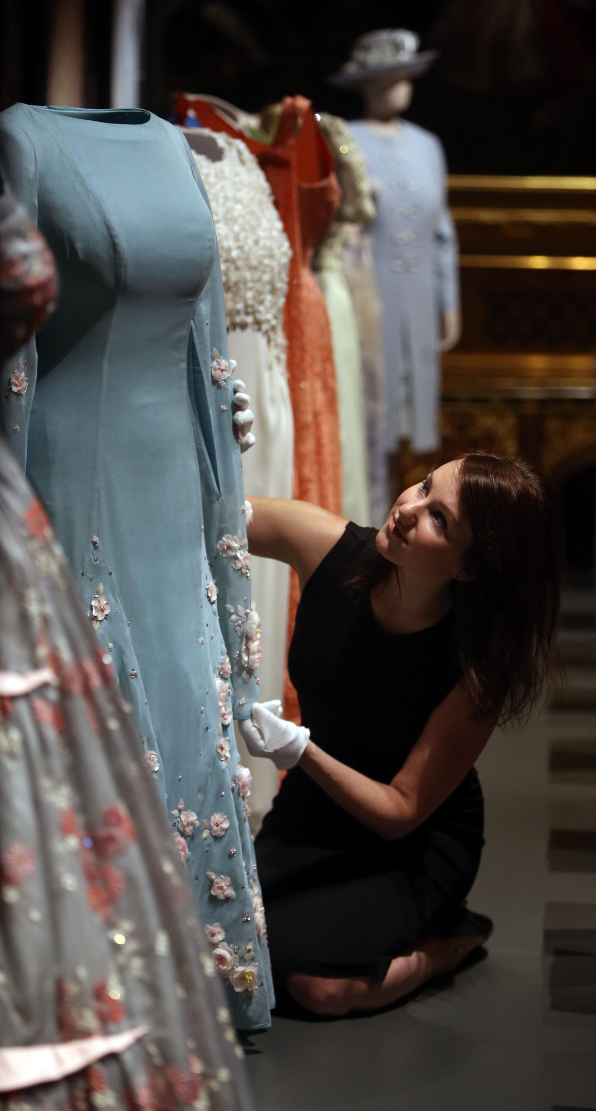 Royal Collection staff member Roxy Gilhooley arranges a selection of dresses worn by The Queen, in the State Dining Room during a press preview for Fashioning a Reign: 90 Years of Style from the Queen's Wardrobe, an exhibition at Windsor Castle in Berkshire (Steve Parsons/PA Wire)