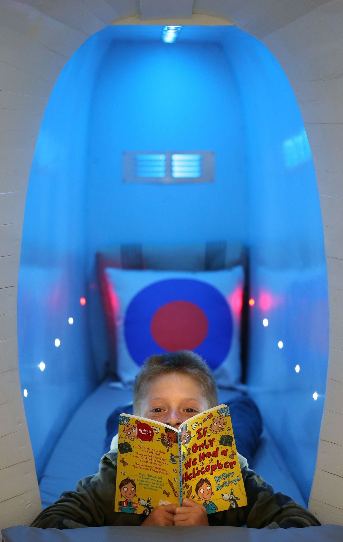 Nine year old Harry Steedman reads a book on the single bed in the tail section of the retired Sea King helicopter (Andrew Milligan/PA Wire)
