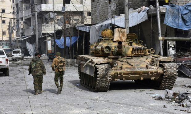 Syrian soldiers pass by a tank where government forces have captured wide areas in eastern Aleppo (SANA via AP)