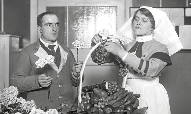 A nurse arranges a basket of fruit and flowers with the help of a patient at King George's Military Hospital  (Topical Press Agency/Getty Images)