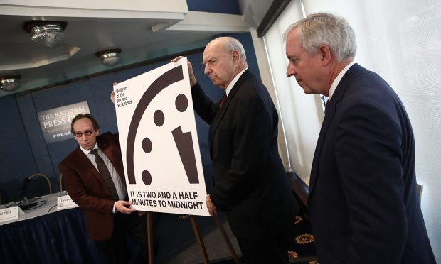"Members of the Bulletin of Atomic Scientists unveil the 2017 time for the ""Doomsday Clock"" (Win McNamee/Getty Images)"