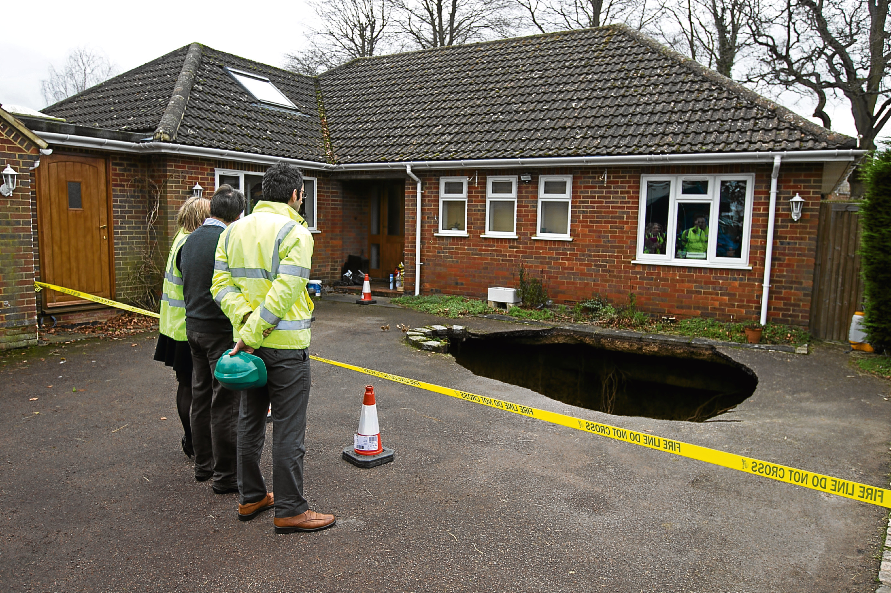 Surveyors at the home of Phil and Liz Conran, in Main Road, Walter's Ash, High Wycombe, Buckinghamshire, after a 30ft-deep sinkhole opened up in the driveway yesterday and swallowed his car.