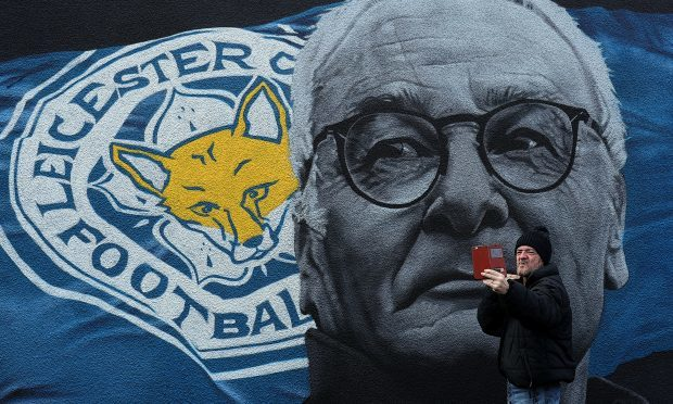 A man takes a picture with a mural of Claudio Ranieri in Leicester city centre (PA)