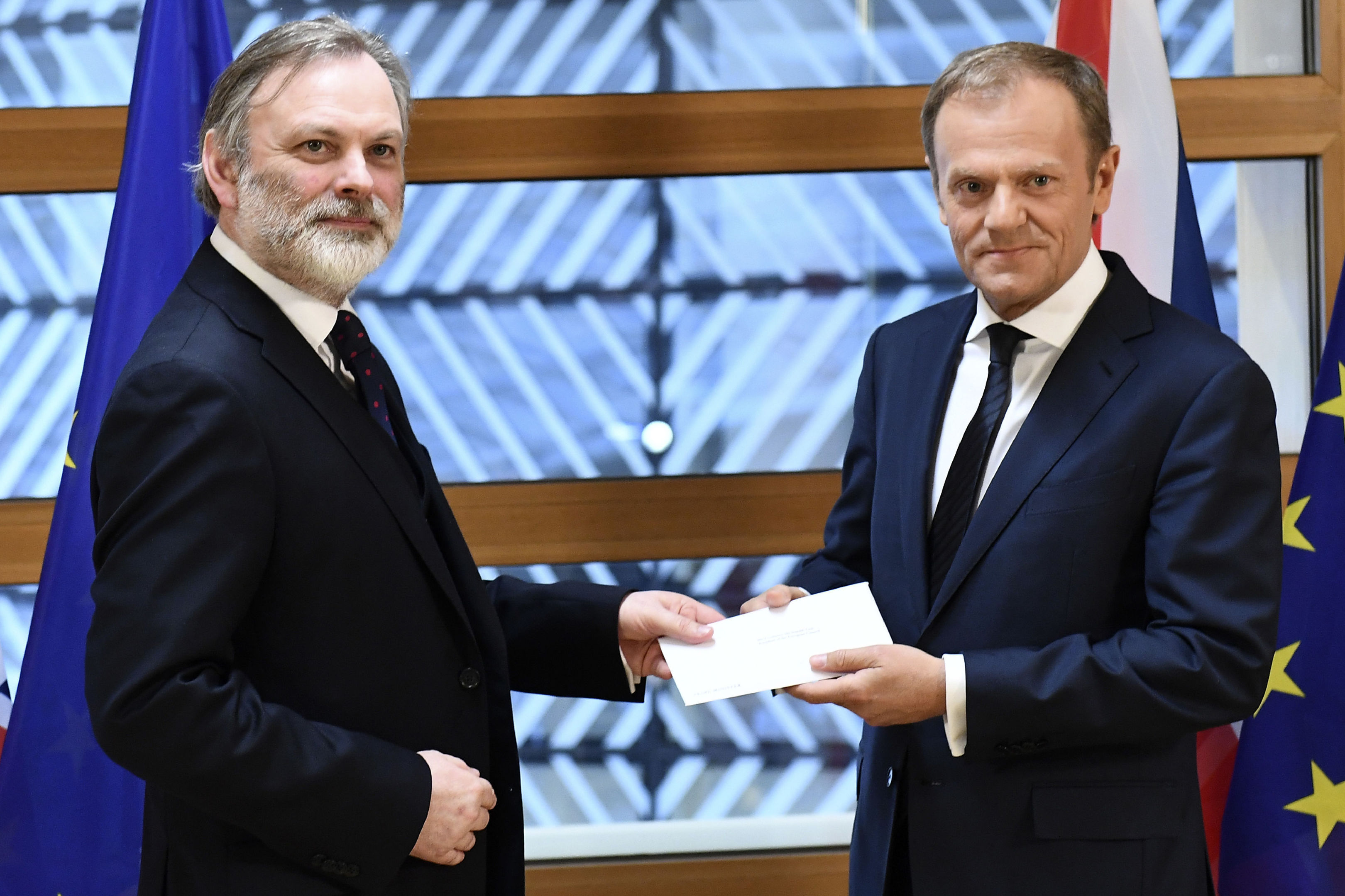 EU Council President Donald Tusk, right, gets Theresa May's formal notice to leave the bloc under Article 50 from UK Permanent Representative to the EU Tim Barrow (Emmanuel Dunand, Pool via AP)