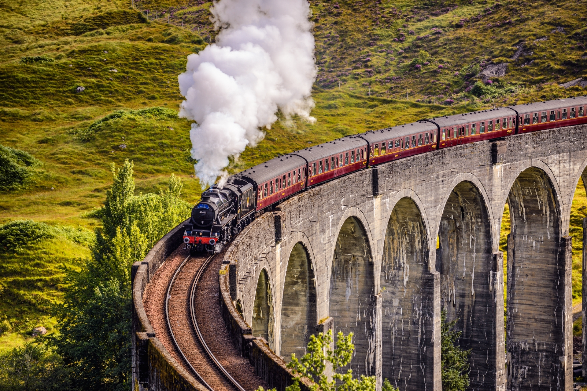 Glenfinnan Railway Viaduct in Scotland with the Jacobite steam train passing over on its way to Mallaig.