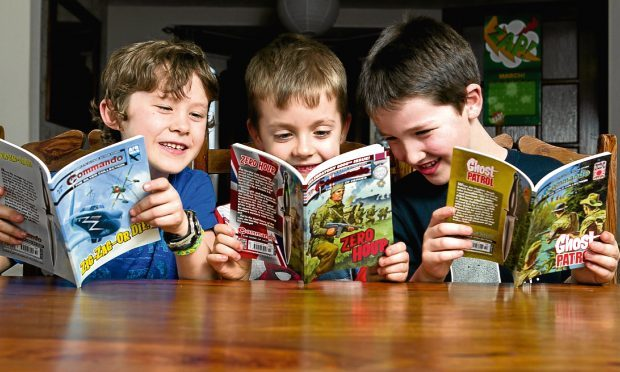 Bailey Dutton (8), Harry Gallagher (7), Evan Butler (7), reading 5000th edition of Commando (Andrew Cawley / DC Thomson)