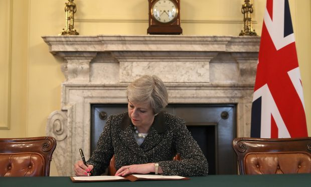 Theresa May signs the official letter to European Council President Donald Tusk (Christopher Furlong - WPA Pool/Getty Images)