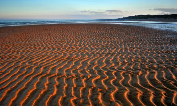 Hypnotic patterns in the sand intensified by the setting sun at Balmedie beach north of Aberdeen  (Alamy)