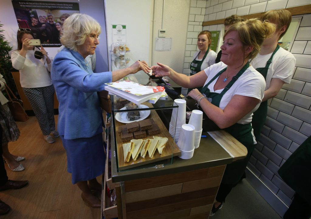 The Duchess of Cornwall, known as the Duchess of Rothesay while in Scotland, speaks to Bonnie Burton (right) as she donates money, during a visit to Social Bite (PA)
