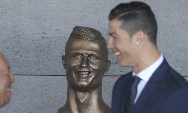 Cristiano Ronaldo and the statue (AP Photo/Armando Franca)