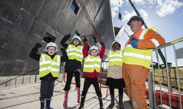 Site foreman Sean McGee and local school pupils (left to right) Dominic Nelson, Sarah McGillivary, Jak Adams and Fiona Okeke celebrating as a crane driver positions a Douglas Fir tree at the highest point of the building during the topping-out ceremony for the V&A Museum of Design Dundee. (Alan Richardson/PA Wire)