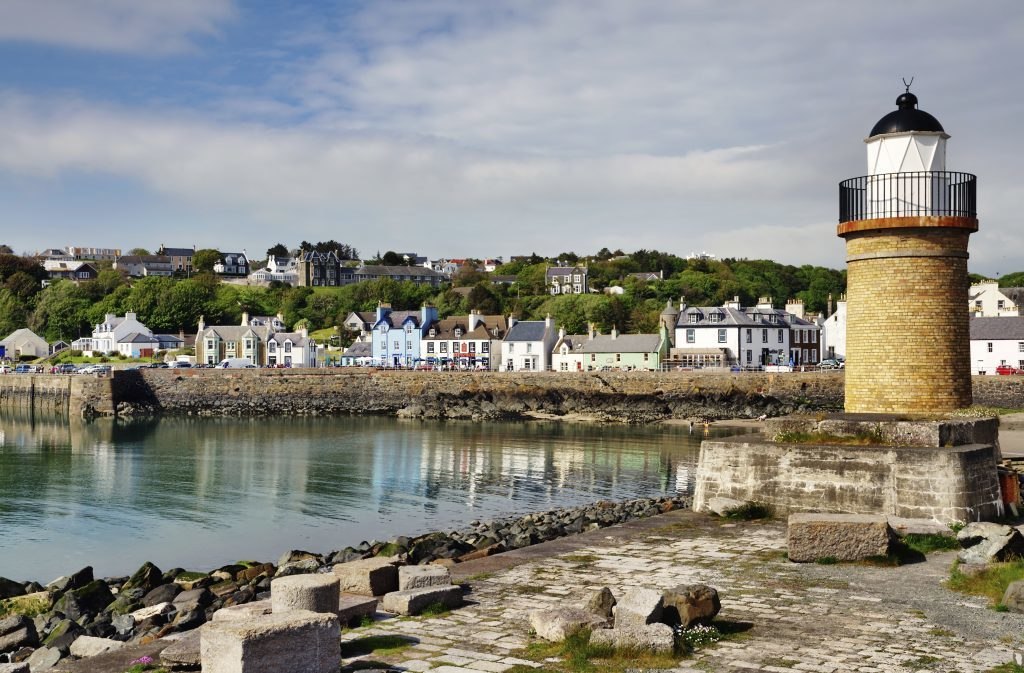 View of the lighthouse and harbour lined with colourful houses at Portpatrick in southwest Scotland on a summers day (iStock)