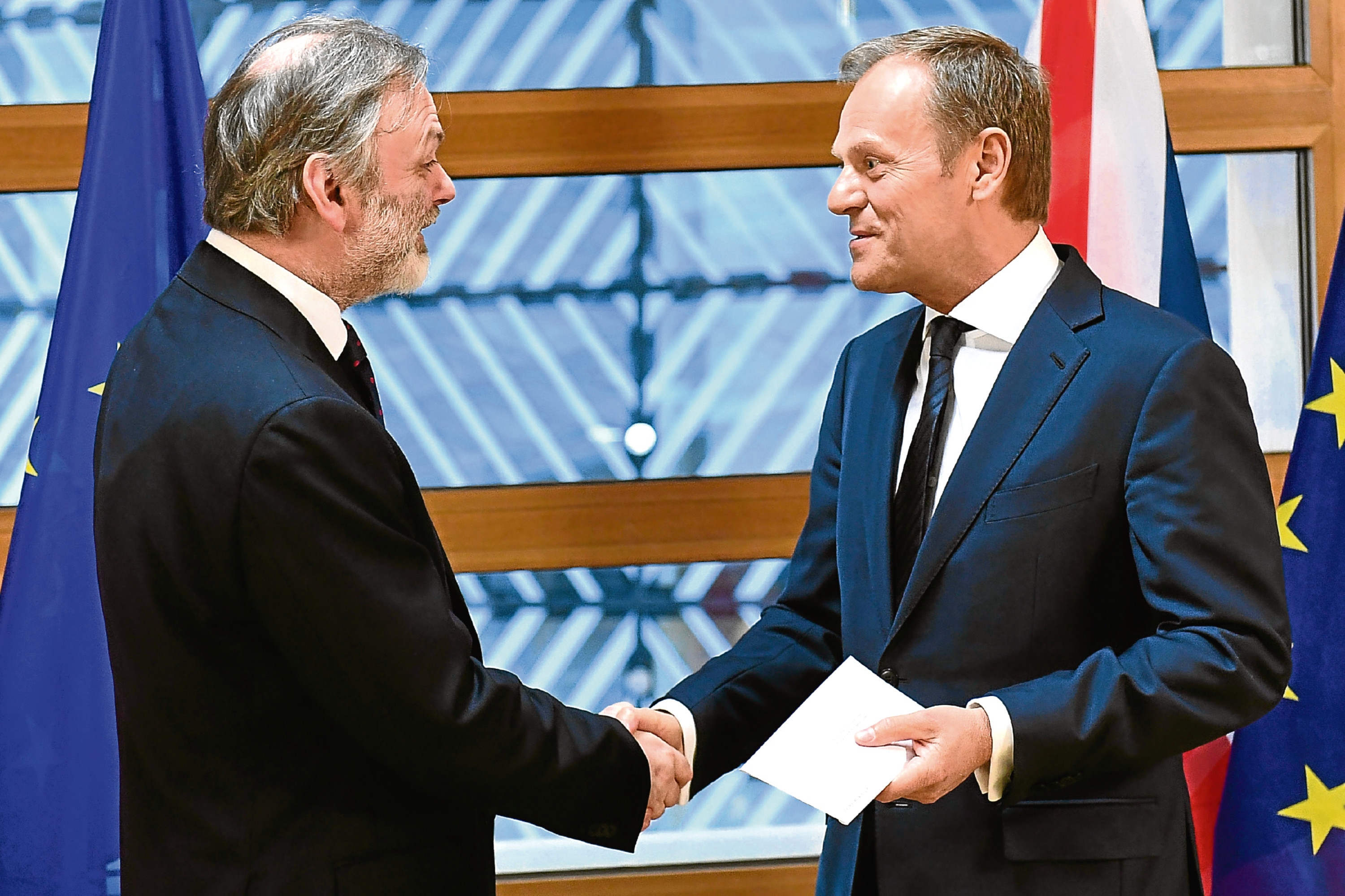 EU Council President Donald Tusk, right, shakes hands with UK Permanent Representative to the EU Tim Barrow after getting British Prime Minister Theresa May's formal notice to leave the bloc under Article 50 of the EU's Lisbon Treaty, in Brussels, Wednesday, March 29, 2017. (Emmanuel Dunand, Pool via AP)