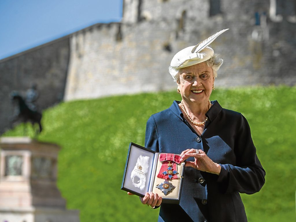 Angela Lansbury poses with her Dame Commander (DBE) medal given to her by Queen Elizabeth II (Steve Parsons - WPA Pool/Getty Images)
