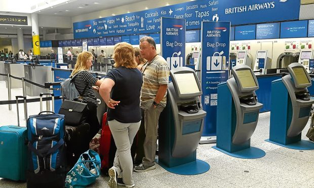 """Passengers at the British Airways check-in desk at Gatwick Airport. The airline says it has cancelled all flights leaving from Heathrow and Gatwick for the rest of today because of a """"major IT system failure"""". (Gareth Fuller/PA Wire)"""