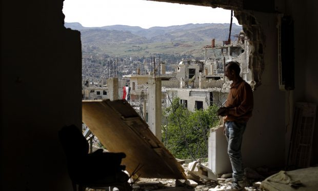 A man checks the damage at the mountain resort town of Zabadani in the Damascus countryside, Syria (AP Photo/Hassan Ammar)