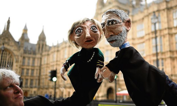Two anti-Brexit activists pose with their hand-puppets depicting British Prime Minister and leader of the Conservative party Theresa May, left, and Britain's Labour party leader Jeremy Corbyn, in front of the Houses of Parliament. (AP Photo/Markus Schreiber)