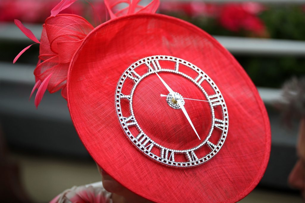 A female racegoer sports a clock themed hat (John Walton/PA Wire)