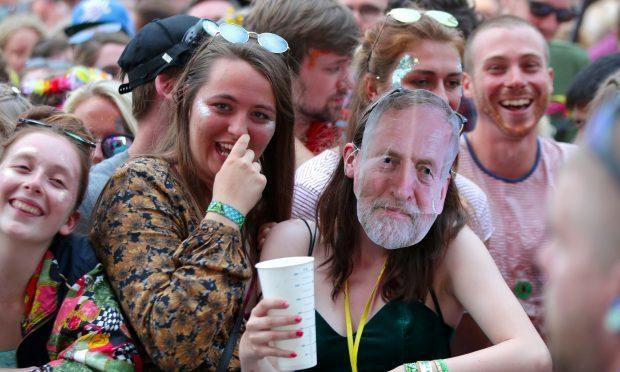 A festivalgoer wearing a Jeremy Corbyn mask at Glastonbury (Yui Mok/PA)