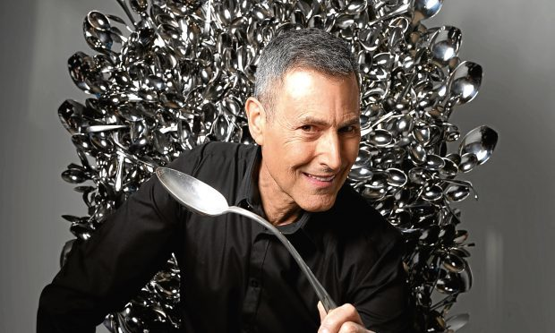 Uri Geller sits on a throne of spoons inspired by the television show Game of Thrones. (David Parry/PA Wire)