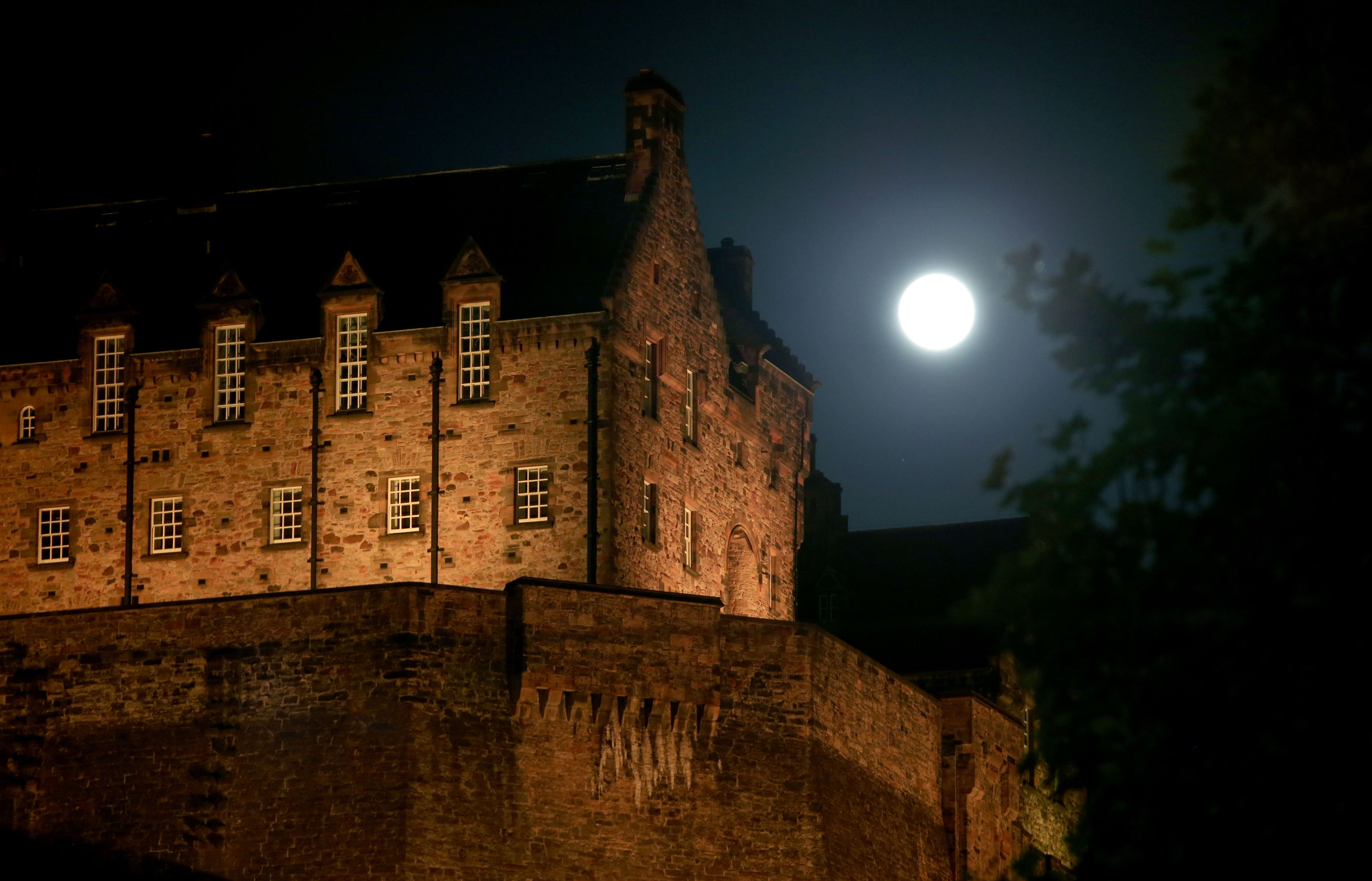 A full moon, known as a Sturgeon Moon in the month of August, rises behind Edinburgh Castle. (Jane Barlow/PA Wire)