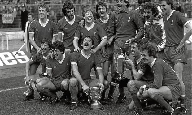 Liverpool team celebrate their football match League Milk Cup Final win over Tottenham Hotpsur, at Wembley in London. * Pictured holding the old League Cup is Captain Graeme Souness and Alan Kennedy (squatting right) holding the new Milk Cup. Goal scorers are : Ronnie Whelan (far left, squatting) and Ian Rush (fourth left standing) (PA)