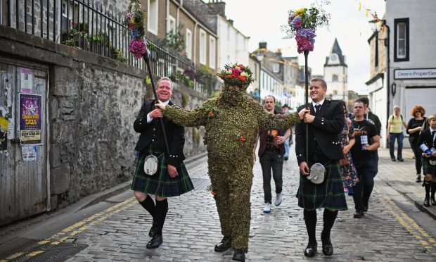 Burryman Andrew Taylor meets residents as he parades through the town in August (Jeff J Mitchell/Getty Images)