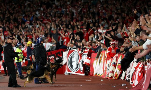 Riot police with dogs stand in front of fans ahead of the match (Richard Heathcote/Getty Images)
