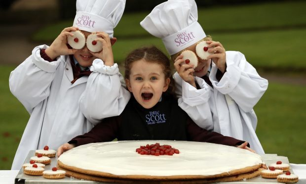 Local children l-r Jamie Gordon (10), Lana Irvine (6) and Joseph Irvine (8) with what is claimed to be the world's largest ever empire biscuit (Andrew Milligan/PA Wire)