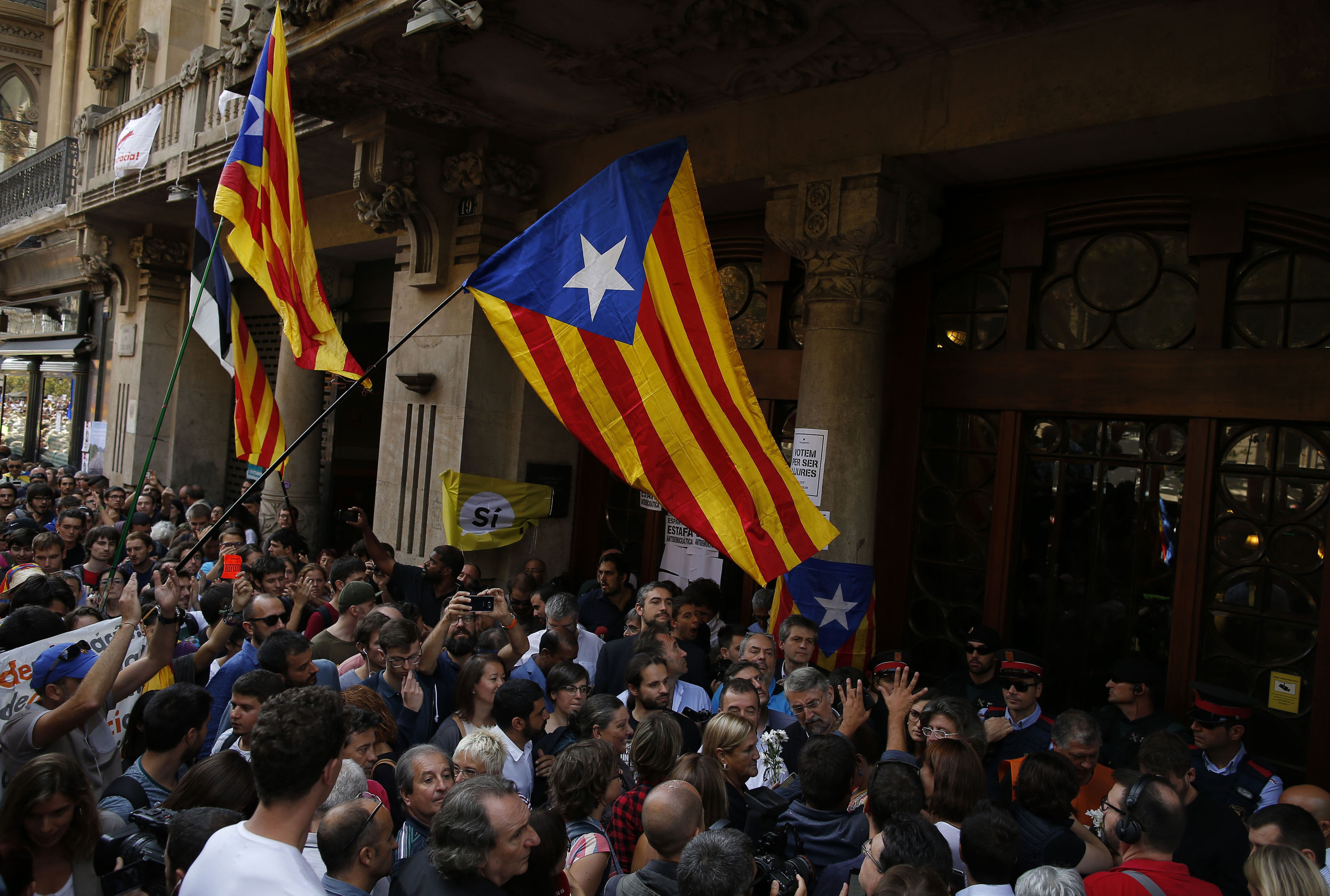 "Pro-independence protestors hold up ""esteladas"", or independence flags, as they gather outside the headquarters of the region's department of economic affairs in Barcelona (AP Photo/Manu Fernandez)"