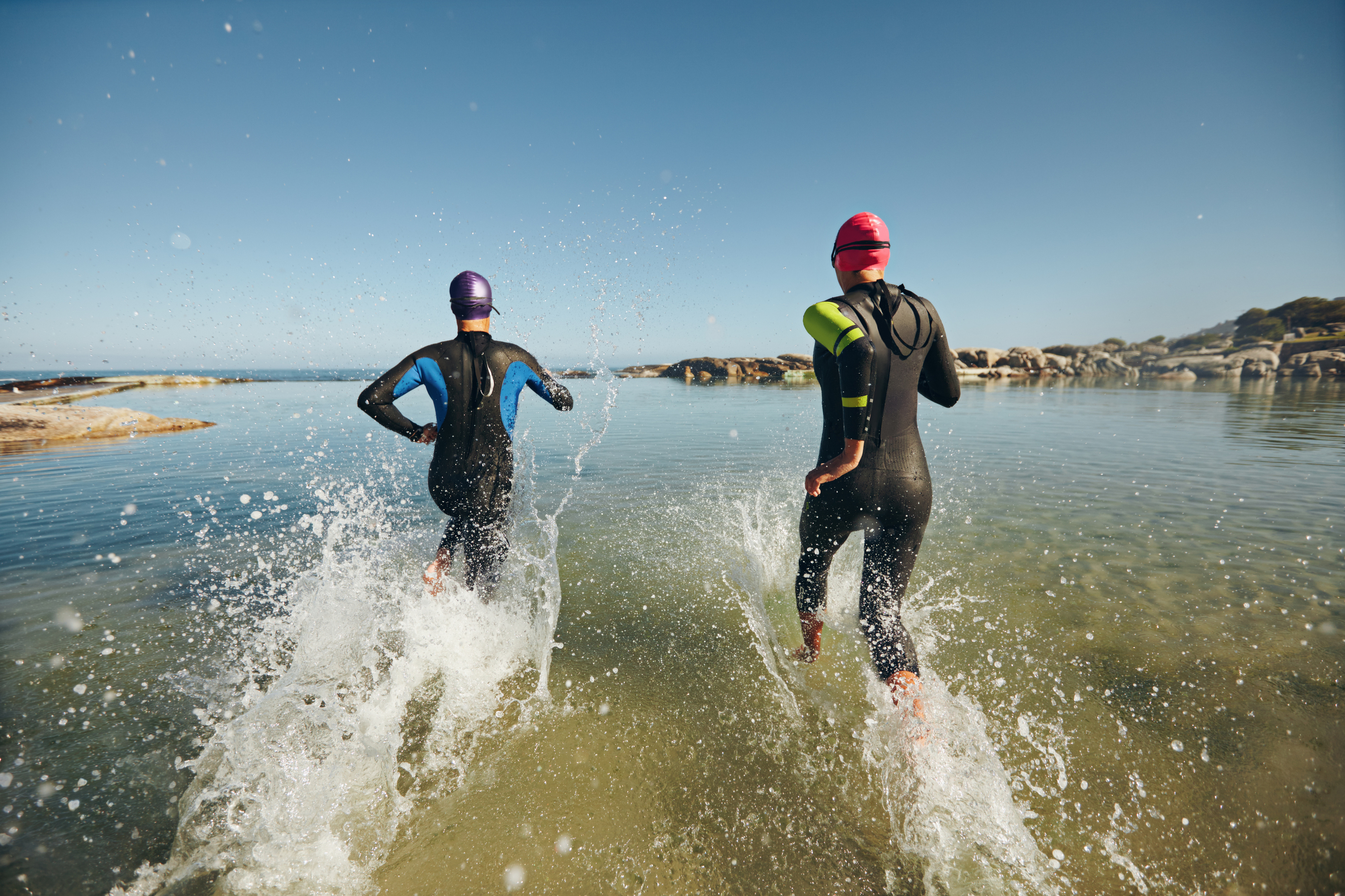 Two athletic swimmers entering the water with their wetsuits on. (iStock)
