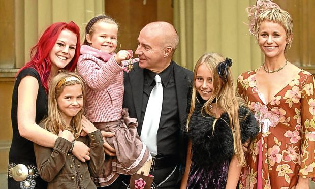 Proud Midge collecting his OBE in 2005 with his wife Sheridan and daughters Molly, Ruby, Flossie and Kitty (Brian Smith / REX / Shutterstock)