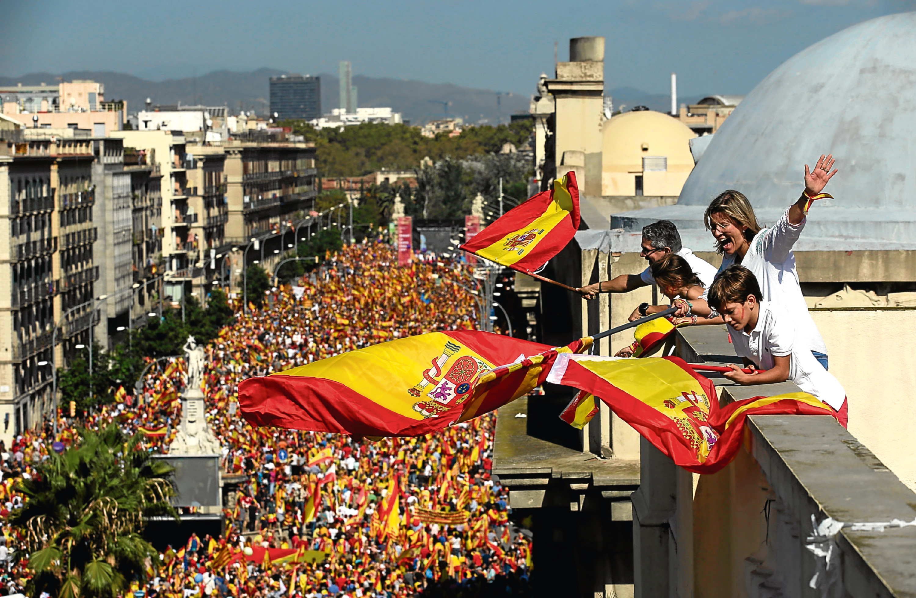 People on a rooftop wave Spanish flags during a march in downtown Barcelona, Spain, to protest the Catalan government's push for secession from the rest of Spain, Sunday Oct. 8, 2017. (AP Photo/Manu Fernandez)
