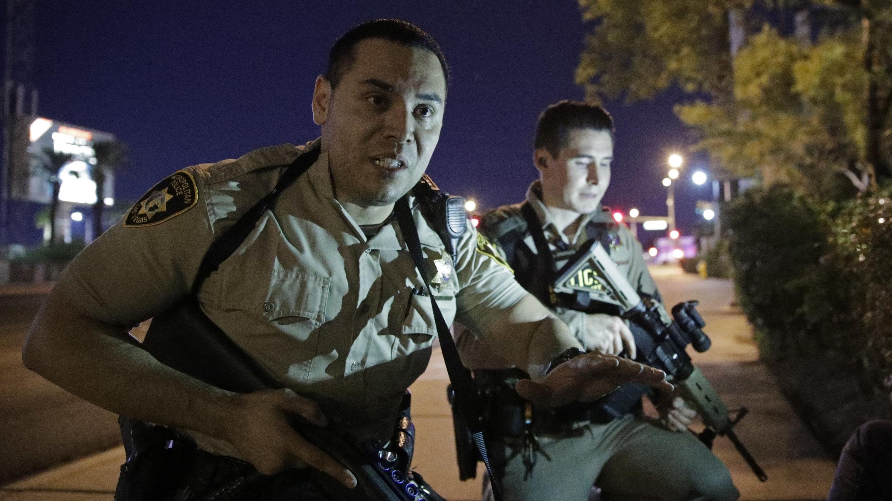 Police officers advise people to take cover near the scene of a shooting near the Mandalay Bay resort and casino on the Las Vegas Strip (John Locher/AP)