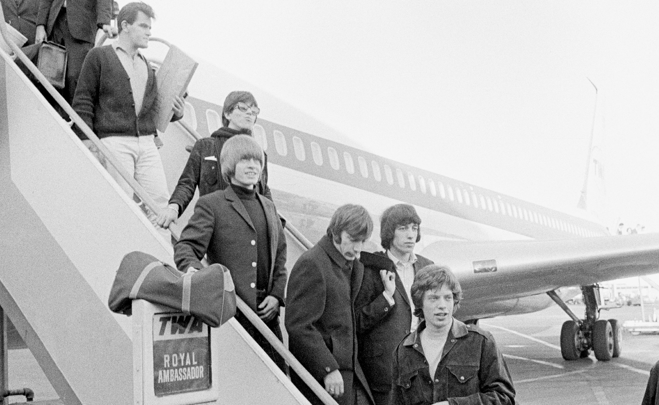 Ian Stewart (top) follows the band off a flight on the Stones' 1965 US tour