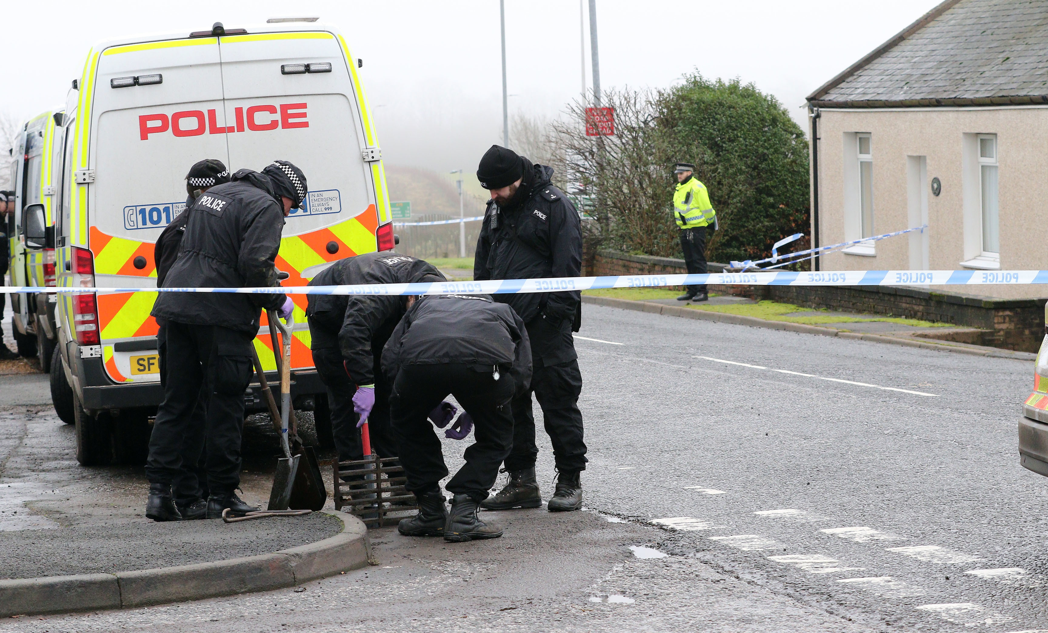 Police at Carrutherstown examining and clearing drains opposite the vicitim's house (Drew Geddes)