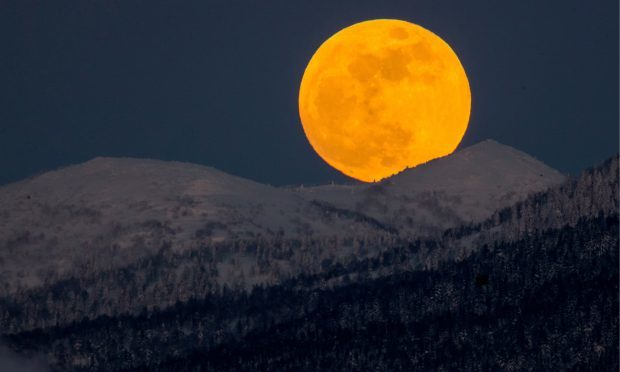 A red supermoon rises over hills near the city of Yuzhno-Sakhalinsk on Sakhalin Island in Russia's Far East. Sergei Krasnoukhov/TASS (Sergei KrasnoukhovTASS via Getty Images)